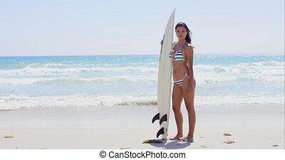 Pretty surfer in striped bikini holding surf board while...