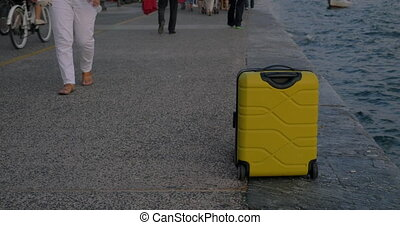 Suitcase on wheels stands on promenade