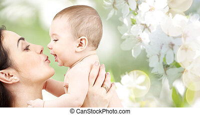 happy mother kissing adorable baby - family, motherhood,...