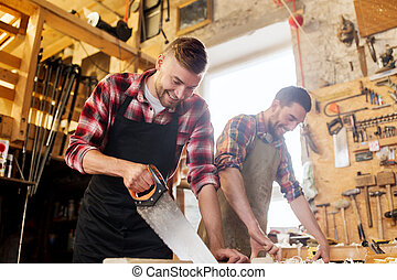 carpenters working with saw and wood at workshop -...