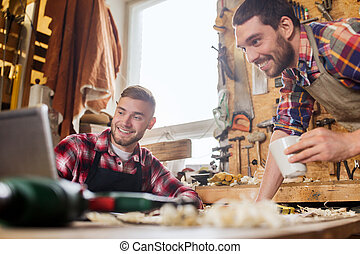 two smiling carpenters with laptop at workshop - profession,...