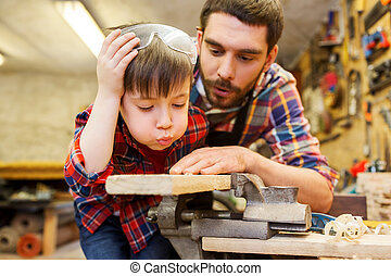 father and little son with wood plank at workshop - family,...