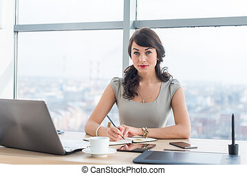 Side view portrait of a businesswoman sitting concentrated,...