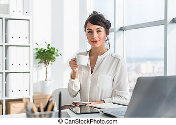 Young attractive office worker drinking cup of tea, having coffee break in the morning, getting ready for work day.