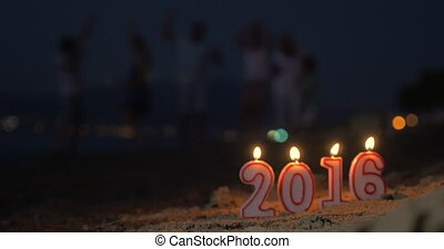 Candles 2016 burns in sand on the beach in evening On blurry...