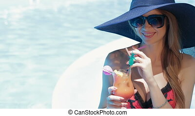 Woman poses with glass of coktail near the swimming pool