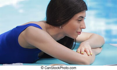 Woman lying on her stomach near the swimming pool