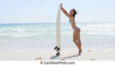 Bathing beauty holds surfboard and smiles at camera while...