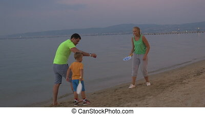 Child and parents playing tennis on the beach - Boy with...