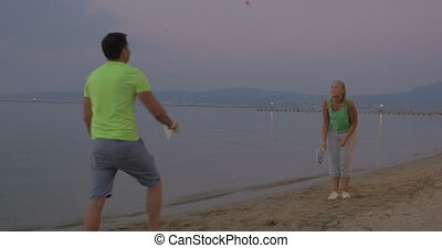 Young couple entertaining themselves with tennis on the...
