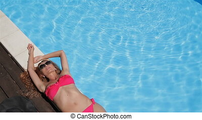 Woman lies on the swimming poolside - Gorgeous caucasian...