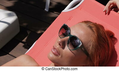 Woman lying in the sun near the swimming pool