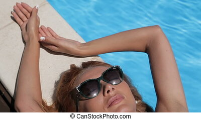 Woman relaxes on the pool edge - Close up of seductive...