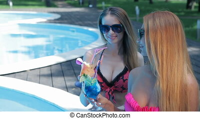 Two women drink cocktails on the swimming poolside