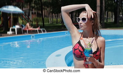 Woman touches her hair near the swimming pool
