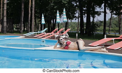 Woman lies on the opposite side of the swimming pool -...