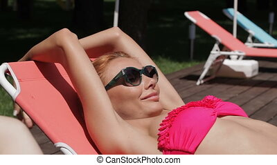 Woman enjoys sunny weather near the swimming pool - Pretty...
