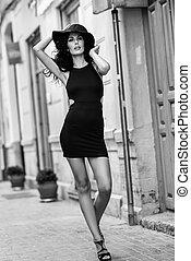 Brunette woman wearing black seductive dress in the street