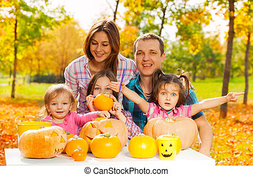 Family carve pumpkins for Halloween in the garden