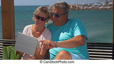 Senior couple using touch pad on waterfront - Senior family...