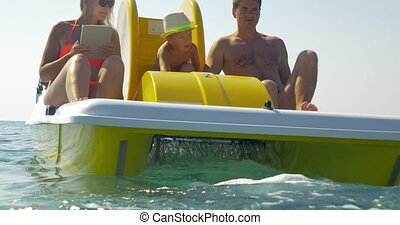Family of three enjoying water ride on pedal boat