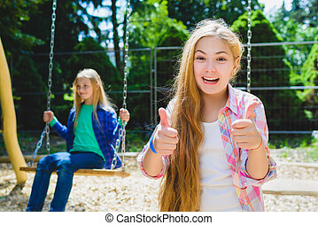 Portrait of happy and smiling child show thumb up at park....