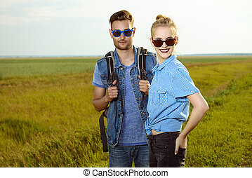 roadside view - Hitchhiking couple Happy young people...