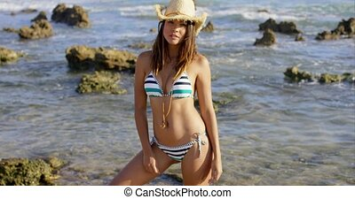 Sexy young woman in a straw hat and bikini standing on a...