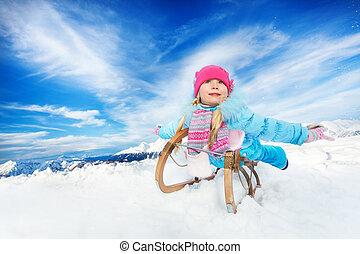 Little girls slide on sledge winter sunny day - Little girl...