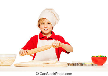 Young baker making dough with rolling pin
