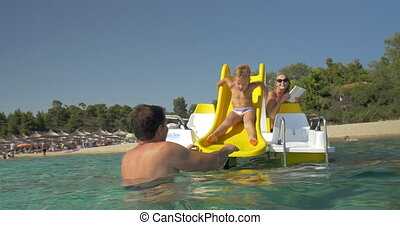 Family having fun in water - Child riding a slider on pedal...