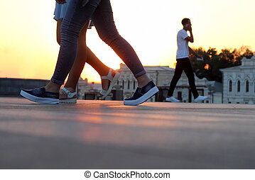legs of people walking at sunset