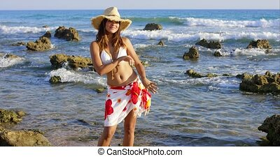 Woman hula dancing on seaweed covered surf while wearing...