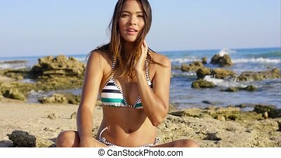 Pretty young woman in a bikini on a rocky beach