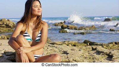 Young woman sitting daydreaming on a beach - Young woman in...