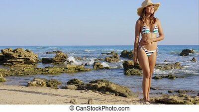 Attractive woman in a bikini walking on a beach - Attractive...