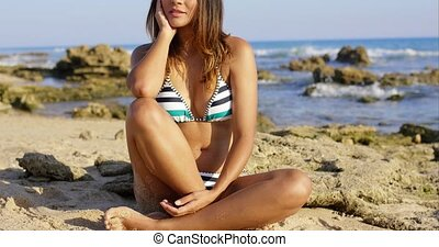 Contented young woman sitting daydreaming - Contented young...