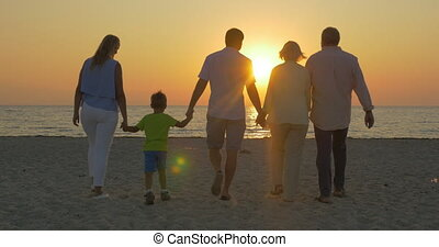 Family looking at golden sunset over the sea - Steadicam...