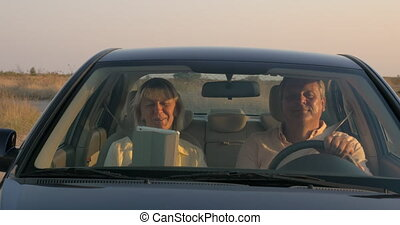 Senior couple traveling by car in the countryside -...