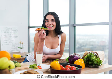 Close-up portrait of woman standing in kitchen, leaning on...
