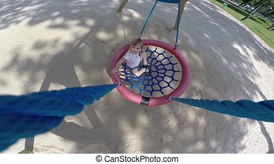 Child on a swing-basket - Cheerful child rides on a swing in...
