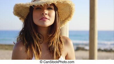 Beauty in white swim suit stares at camera wearing straw hat...