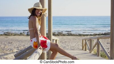 Happy vivacious young woman at the beach sitting on the...