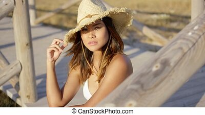Young woman sitting on a wooden promenade in a sunhat and...