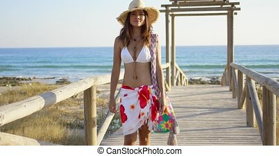 Smiling woman on a wooden beachfront promenade - Smiling...