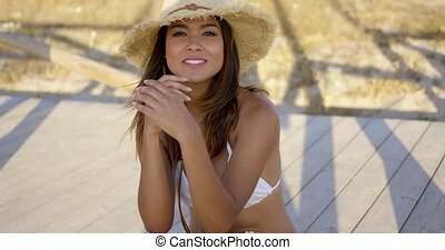 Smiling brown haired beauty sits on boardwalk while wearing...
