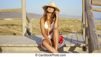 Pretty young woman enjoying a day at the seaside sitting in...