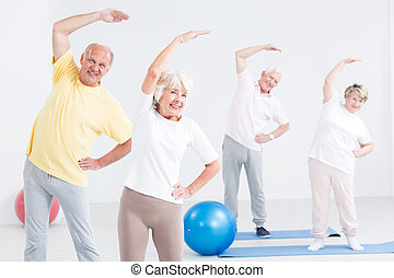 Why not exercising together? - Happy seniors during workout...