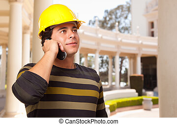 Handsome Hispanic Contractor with Hard Hat Talking on His...