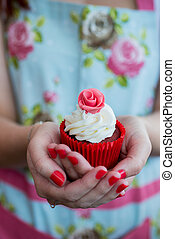Woman in Floral dress with painted nails holding rose cupcake